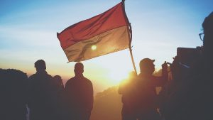 silhouette of people holding red and yellow flag