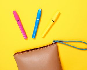 three mascara tubes (pink,blue,yellow) spilling out of small tan purse on yellow plain backdrop