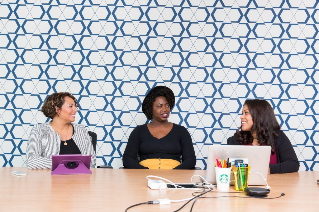 three women sitting on chairs front of table