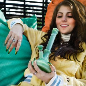 woman in yellow jacket holding green bong